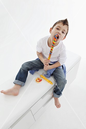 A little boy eating a giant lolly