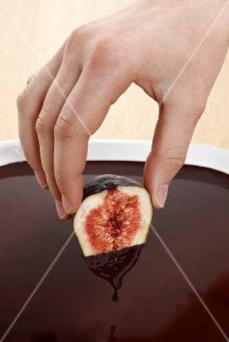 Hand dipped fig in chocolate sauce