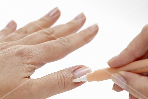 A woman applying a care product to her nail bed