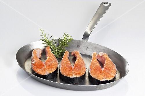 Fresh salmon steaks in a frying pan