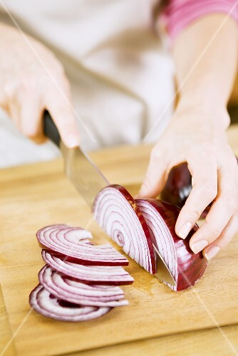 Woman Slicing Red Onion on Cutting Board