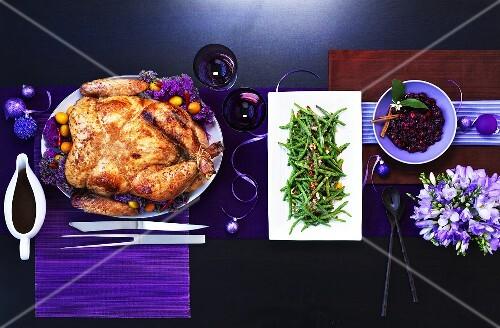 Chinesischer Putenbraten mit grünen Bohnen auf einem Tisch mit lila Deko (Von Oben)