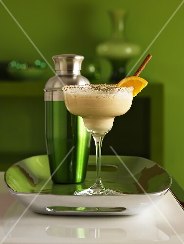 Frozen martini in a glass with sugar on the rim of the glass and a shaker
