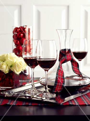 Red wine in glasses and carafe on a table decorated for Christmas