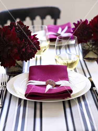 A place setting with a white plate and a pink napkin