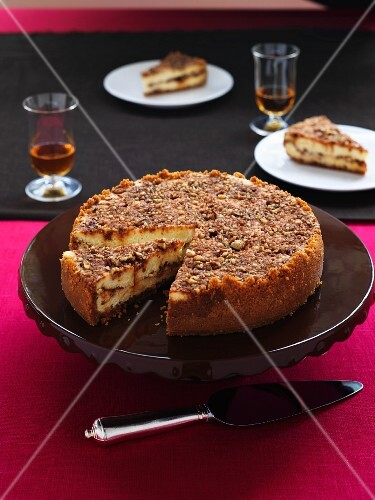 Praline cheese cake on a cake platter with a pie slice