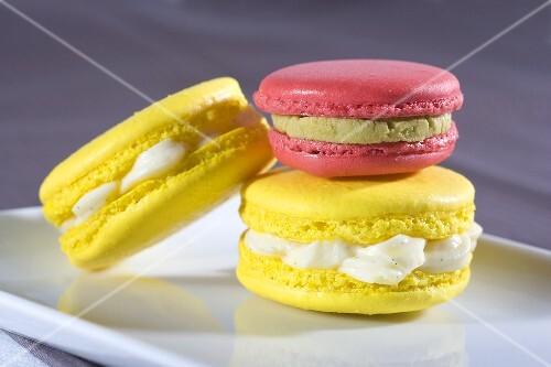 Yellow macaroons with vanilla cream, pink macaroon with pistachio cream