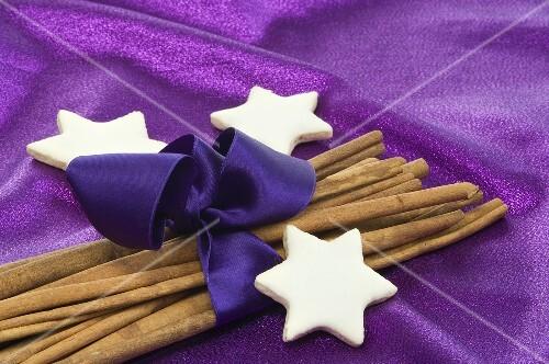 Cinnamon stars with cinnamon sticks wrapped with purple ribbon