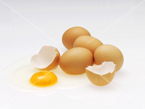Several brown eggs, one cracked