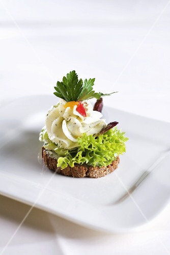 A canape with cream cheese and lettuce