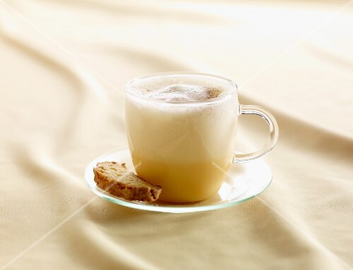 Spiced eggnog in a glass cup with biscotti