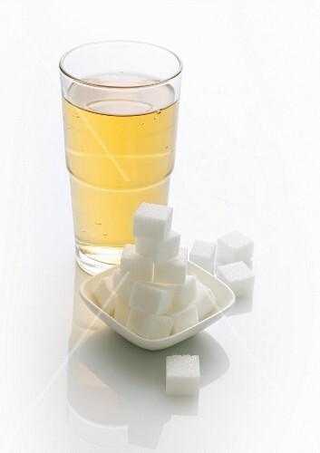 A glass of lemonade and sugar cubes