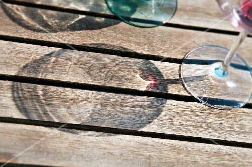 Shadows of wine glasses on a wooden surface