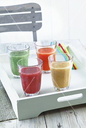 Four smoothies on a tray on a wooden table