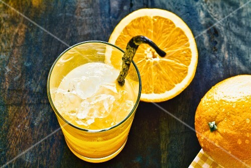 Orange juice with a vanilla pod and ice cubes