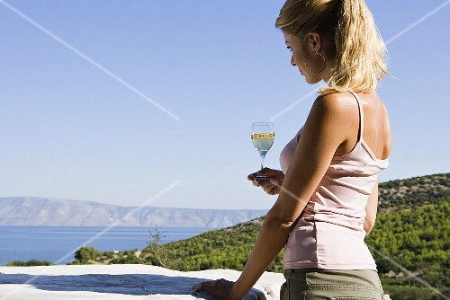 A woman holding glass of white wine and looking out to sea