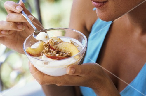 A young woman eating yoghurt with nectarines and nuts