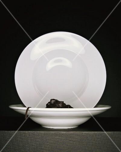 Black ribbon pasta with two white pasta plates
