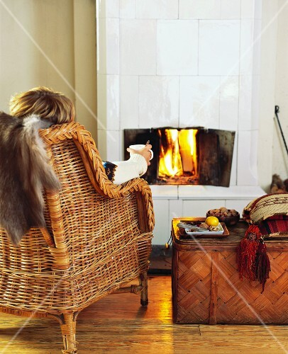 Person in cane chair with cup of tea in front of open fire