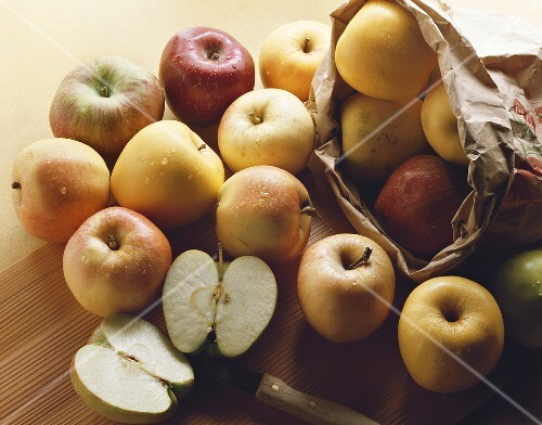 Various types of apples out of a paper bag