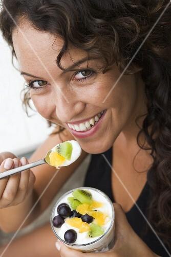 Woman eating yoghurt with fresh fruit