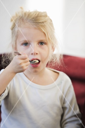 A little blonde girl eating a spoonful of yoghurt