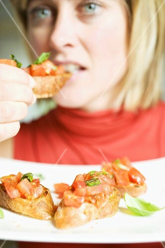 Woman eating bruschetta with fresh basil