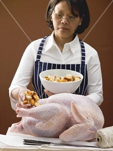 Frau füllt Truthahn mit Brotwürfeln