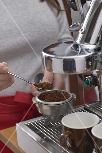 Woman filling filter holder with ground espresso coffee