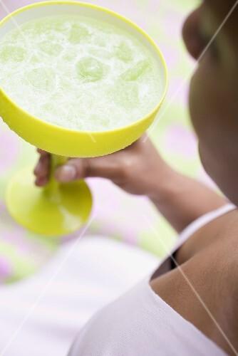 Frau hält grünes Glas mit Cocktail