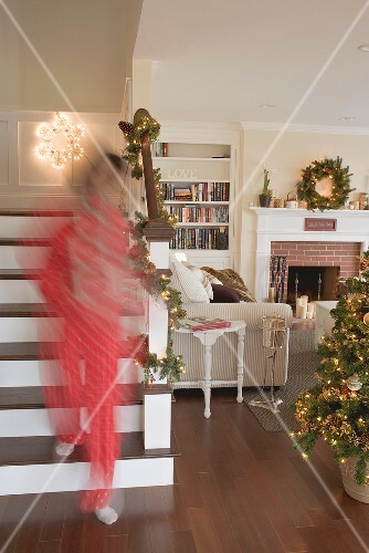 Woman carrying boxes of Christmas decorations into living room