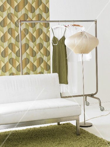 Sofa, clothes rack and standard lamp in a room