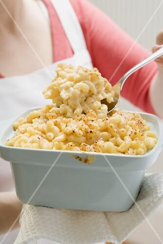 Frau serviert Macaroni and Cheese