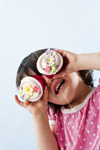 Girl with two cupcakes in front of her eyes