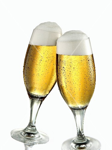 Two glasses of pils clinking together