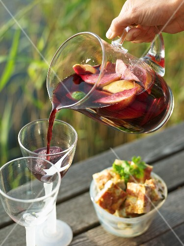 Man pouring sangria into glasses on a landing stage