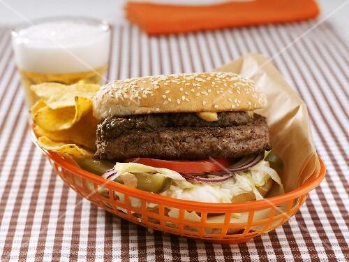 Hamburger and crisps in plastic basket, glass of beer