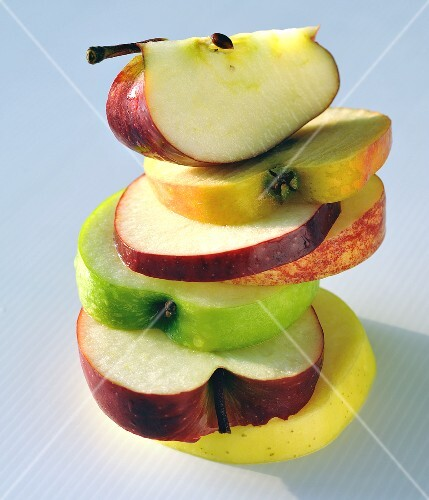 Slices of different apples, stacked