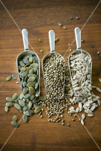 Pumpkin seeds, sesame seeds and hemp seeds in three scoops