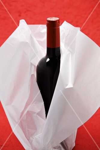 A bottle of red wine wrapped in tissue paper
