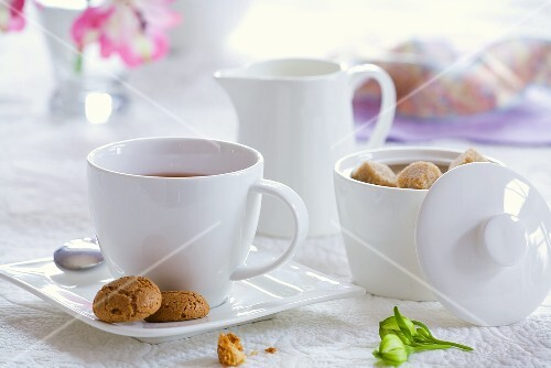 A cup of tea with sugar bowl, milk jug and biscuits