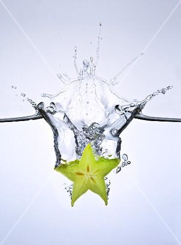 Slice of carambola falling into water
