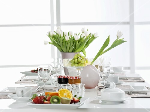 A table laid for breakfast with white tulips and fruit