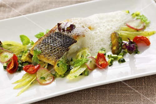 Fried branzino (sea bass) with spring vegetables and foam sauce