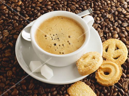 A cup of coffee with sugar cubes and biscuits