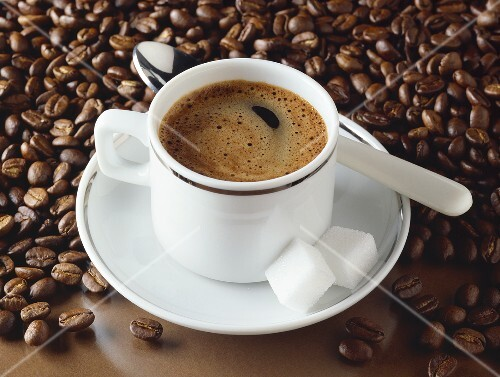 A cup of espresso and coffee beans