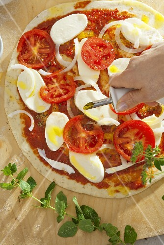 Sprinkling pizza with olive oil