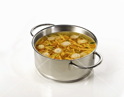 Clear broth with noodles and dumplings in pan