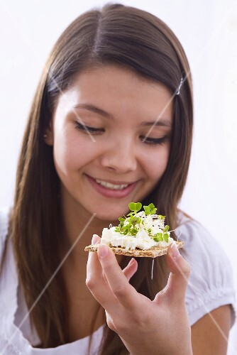 Girl holding crisp bread with cottage cheese and cress
