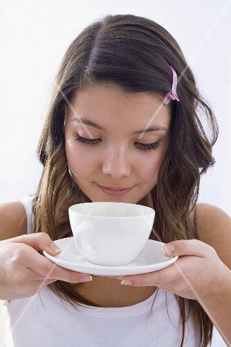 Girl smelling a scented cup of tea